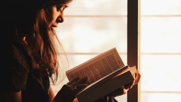 woman reading a book beside the window