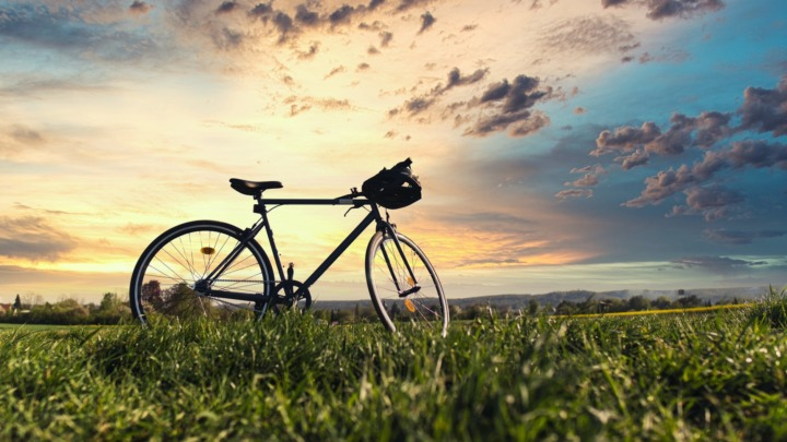 black bicycle on green grass field under cloudy sky